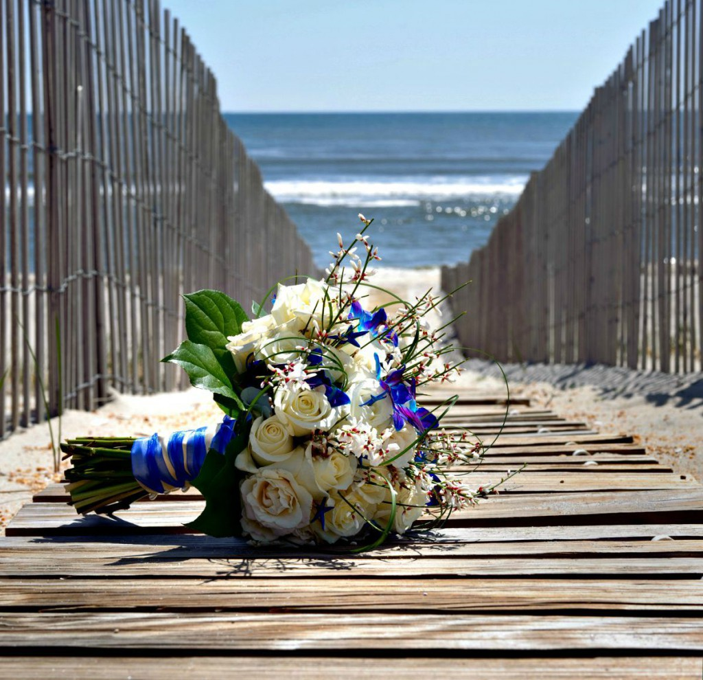 Wedding bouquet resting on a wooden boardwalk leading to the beach and ocean