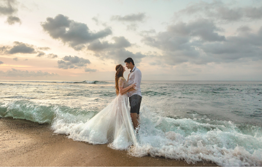 newly married couple standing in the ocean waves
