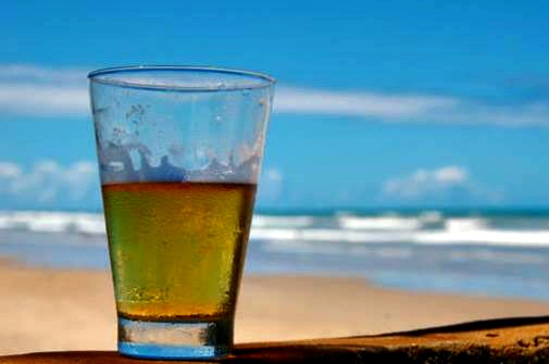 Baytowne Wharf Beer Fest glass of beer on the beach with the Gulf in the background