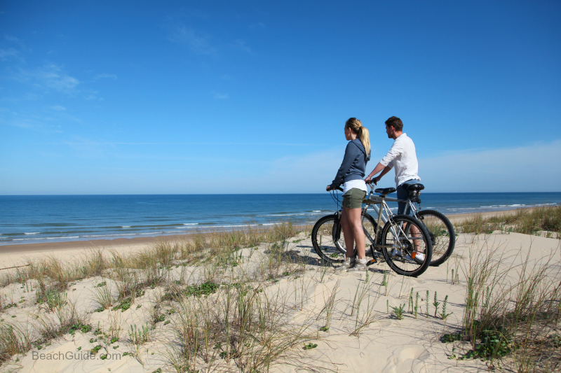 Couple enjoying a winter bike ride on Hwy 30a beaches in Florida.