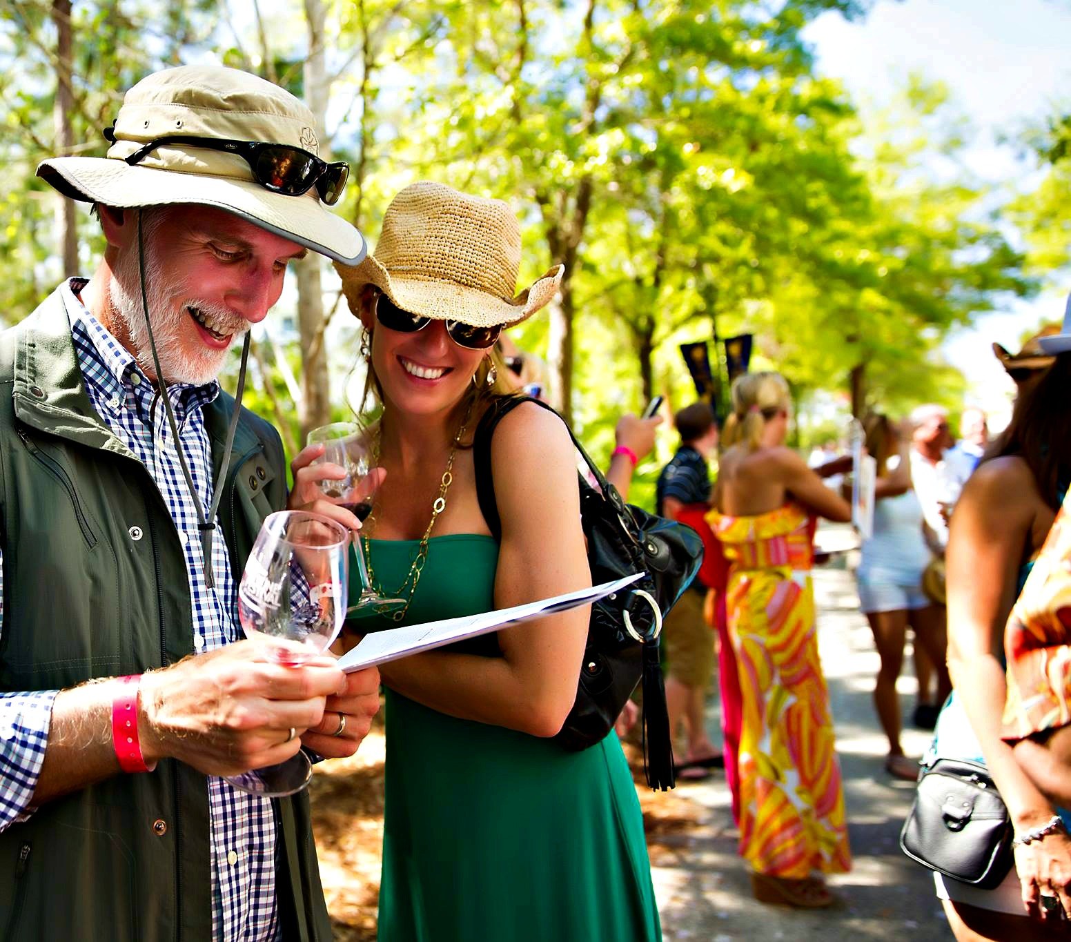Couple reading program on a sunny day at Sandestin Wine Festival