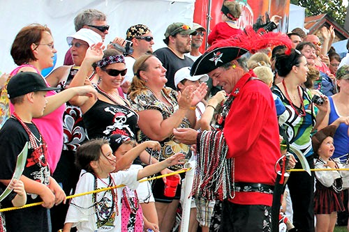 Billy Bowlegs Festival Pirate handing out beads to the crowd