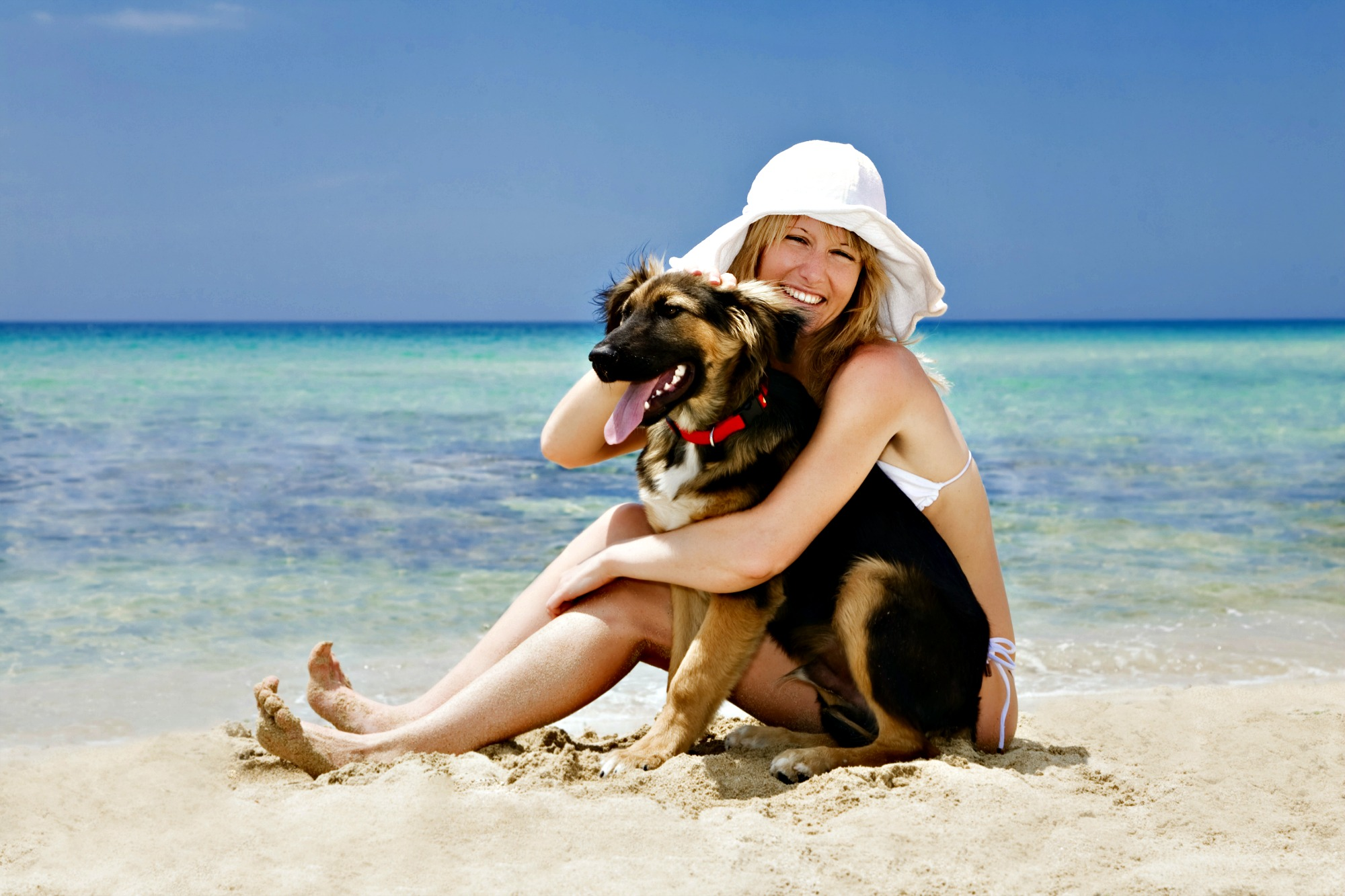 Woman sitting in the surf cuddling her dog