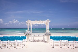Beach wedding setup with blue-covered white chairs and arch decorated with sand dollars