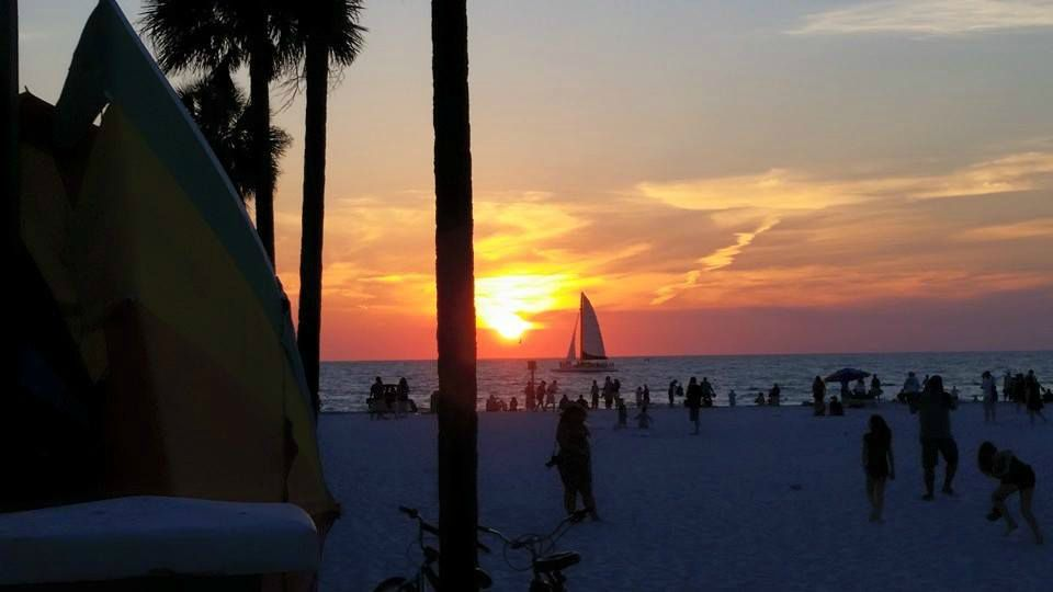 Gulf sunset, a sailboat in the Gulf, and people on the beach at Sunsets at Pier 60 in Clearwater Beach