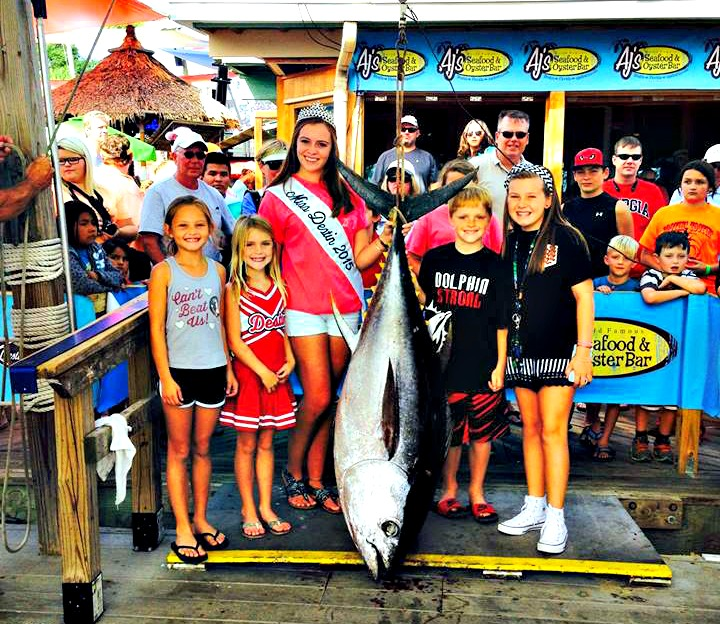 Children and Miss Destin standing on the dock with a giant tuna at the Destin Fishing Rodeo