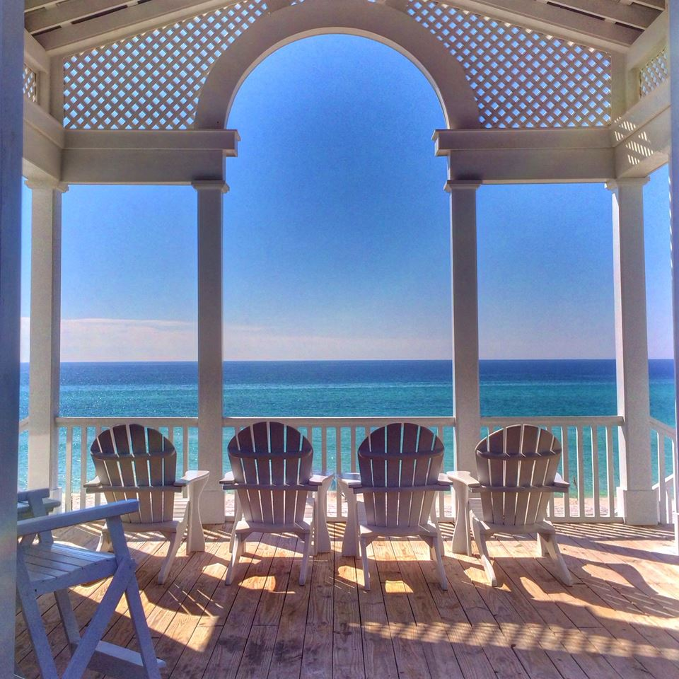 Columned and arched beachfront gazebo with four Adirondack chairs and a view of the Gulf