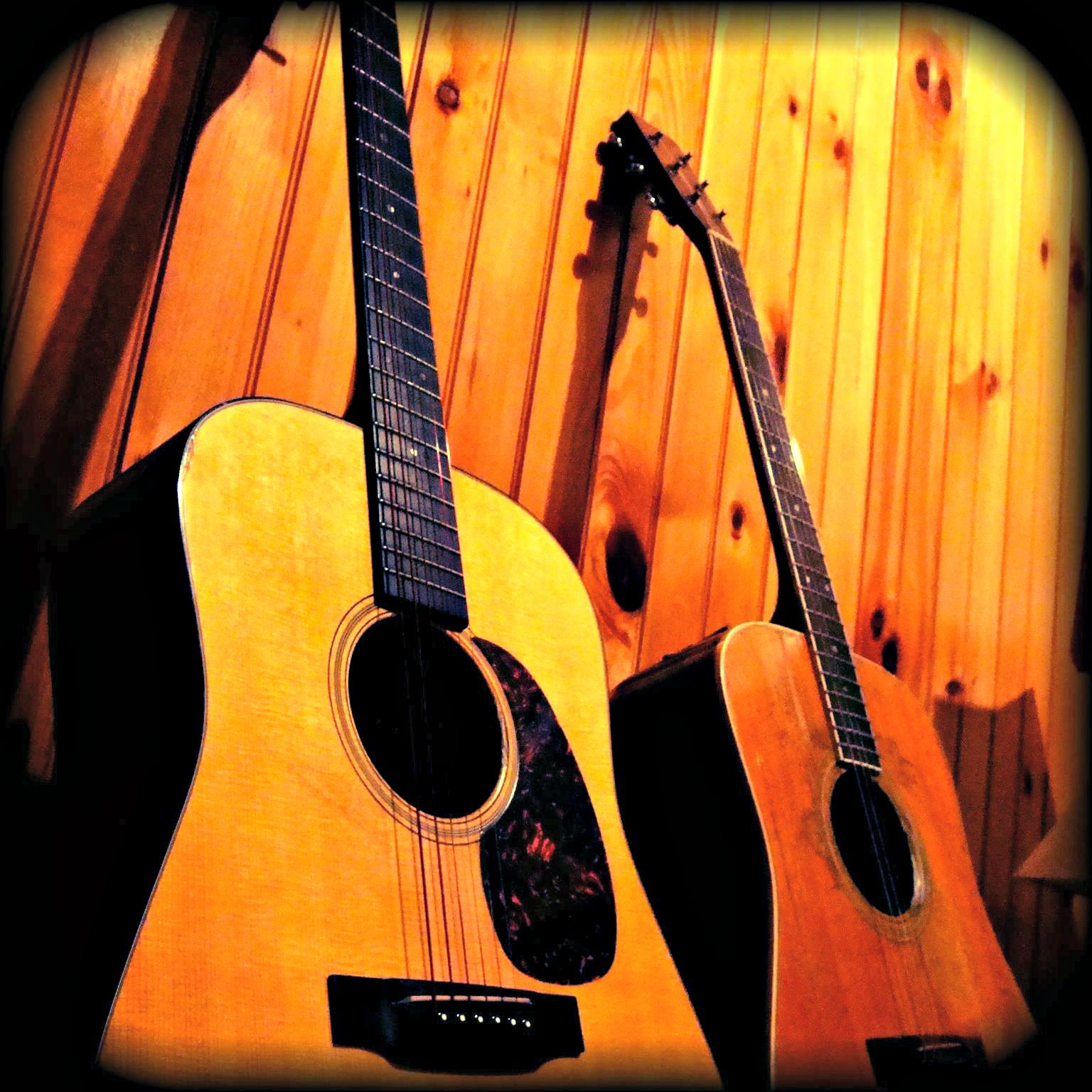 Frank Brown International Songwriters' Festival two guitars propped against a paneled wall