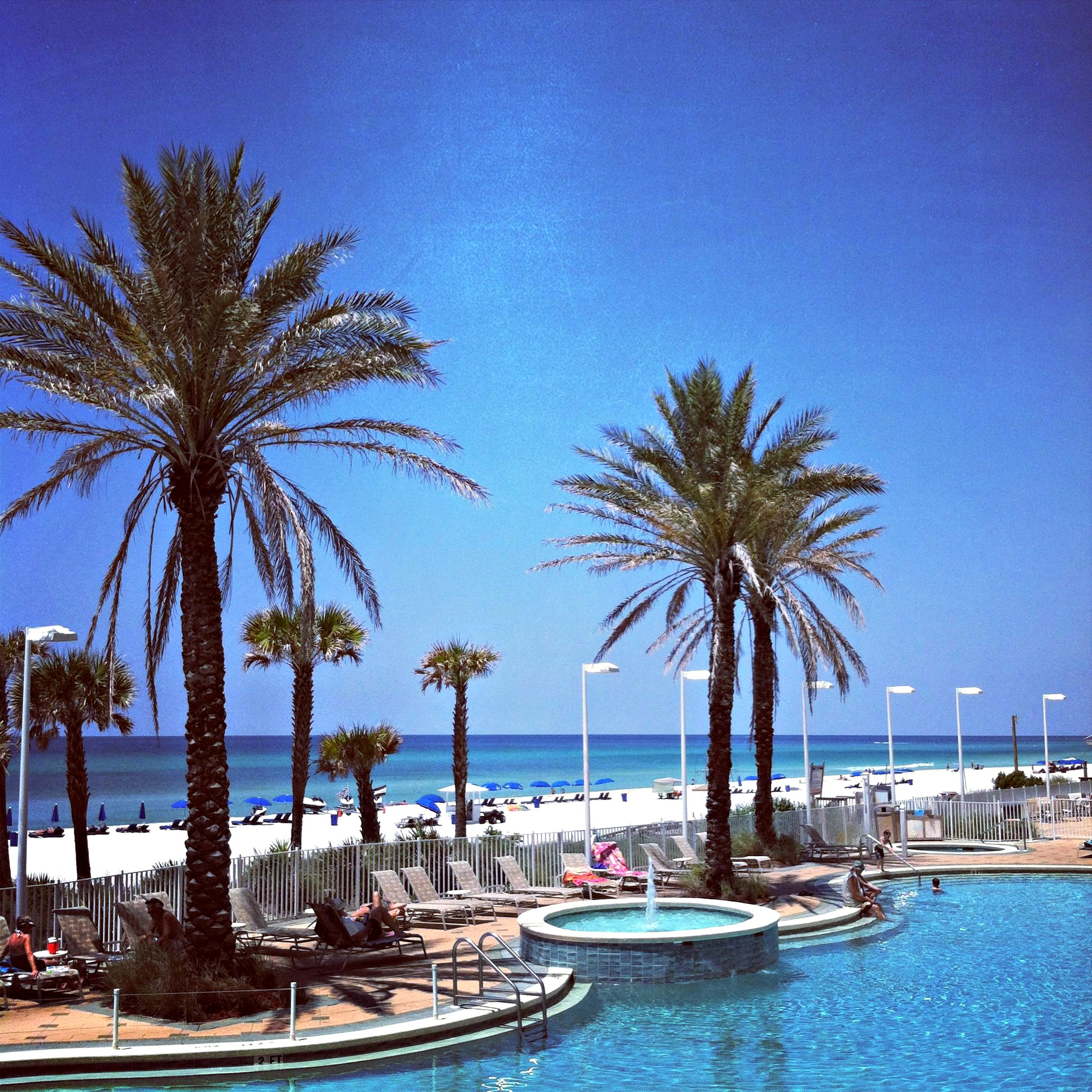 Palm trees and attractive landscaping frame the Gulf-front pool at Boardwalk Beach Resort in Panama City Beach.