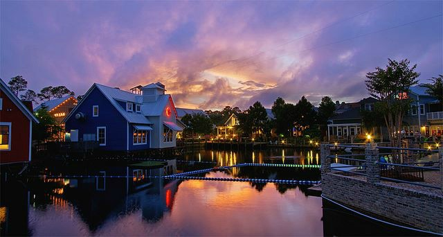 Evening shot of Sandestin's Village of Baytowne Wharf with lights reflected in the waters of the bay