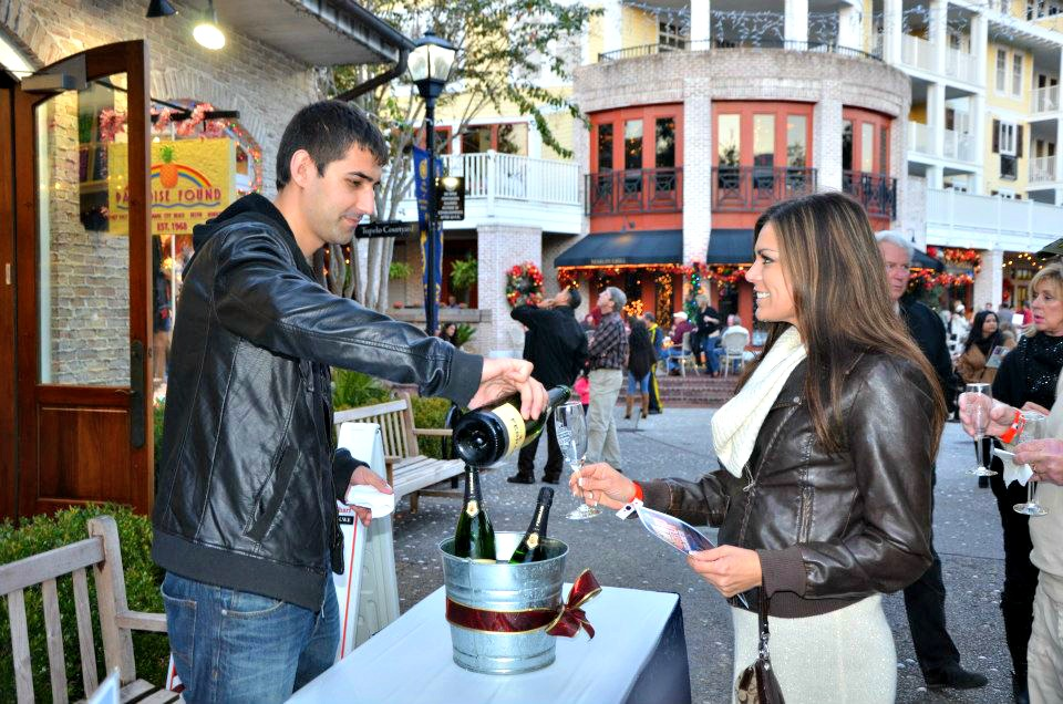Woman getting a champagne sample in a scene at Village of Baytowne Wharf during the Sandestin Sparkling Wines and Holiday Lights wine tasting