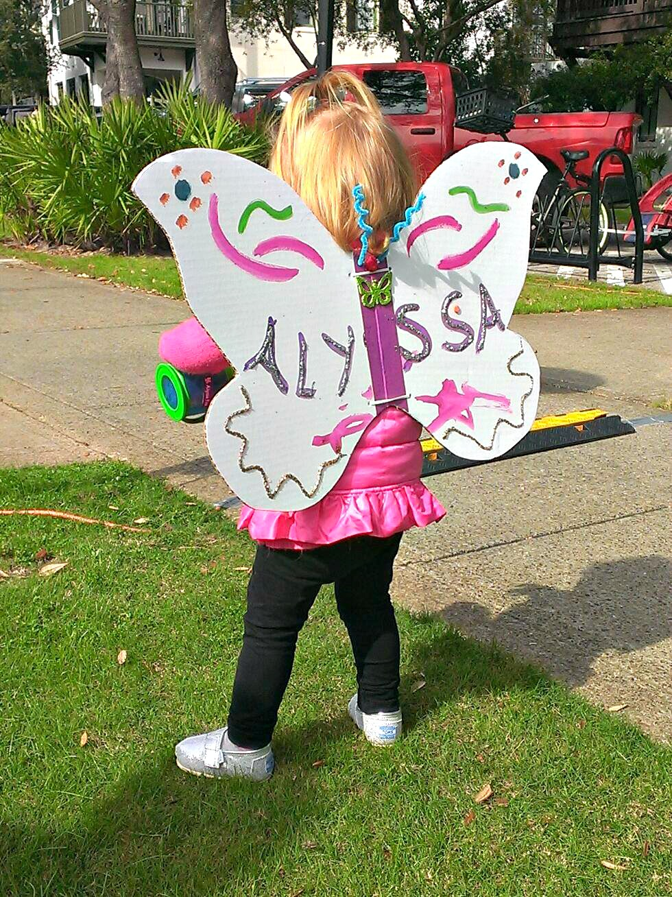 Little girl in pink tunic, black leggings, and posterboard butterfly wings at Fluttery Festival in Rosemary Beach for Highway 30-A arts blog