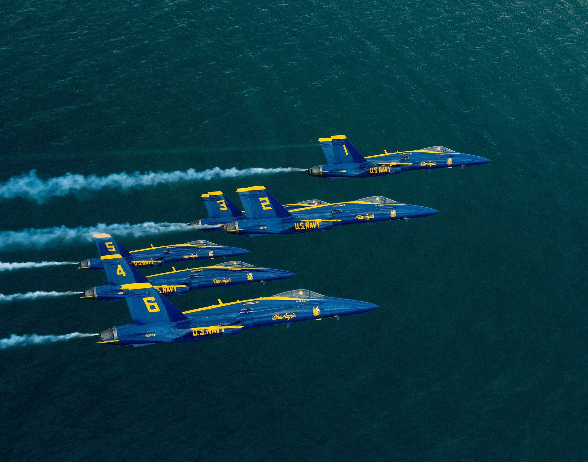 Six Blue Angels jets fly in formation over the Gulf of Mexico in Pensacola Beach FL.