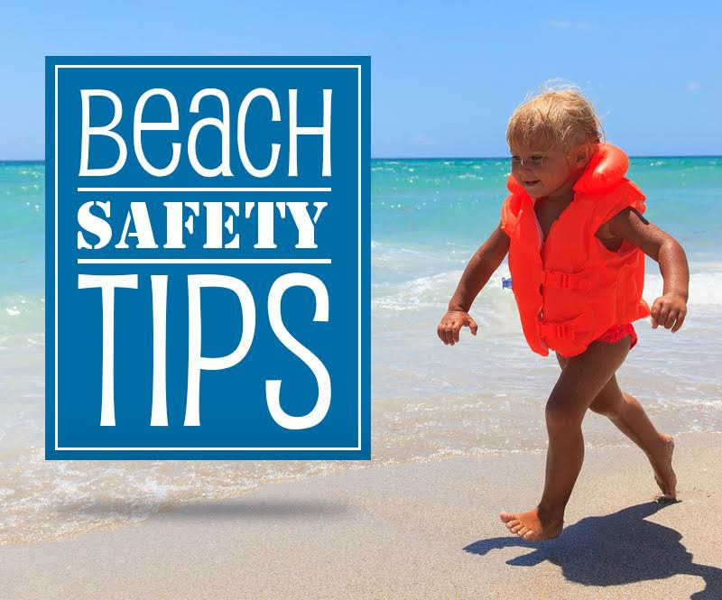 Blond-haired child on the beach wearing a red life jacket