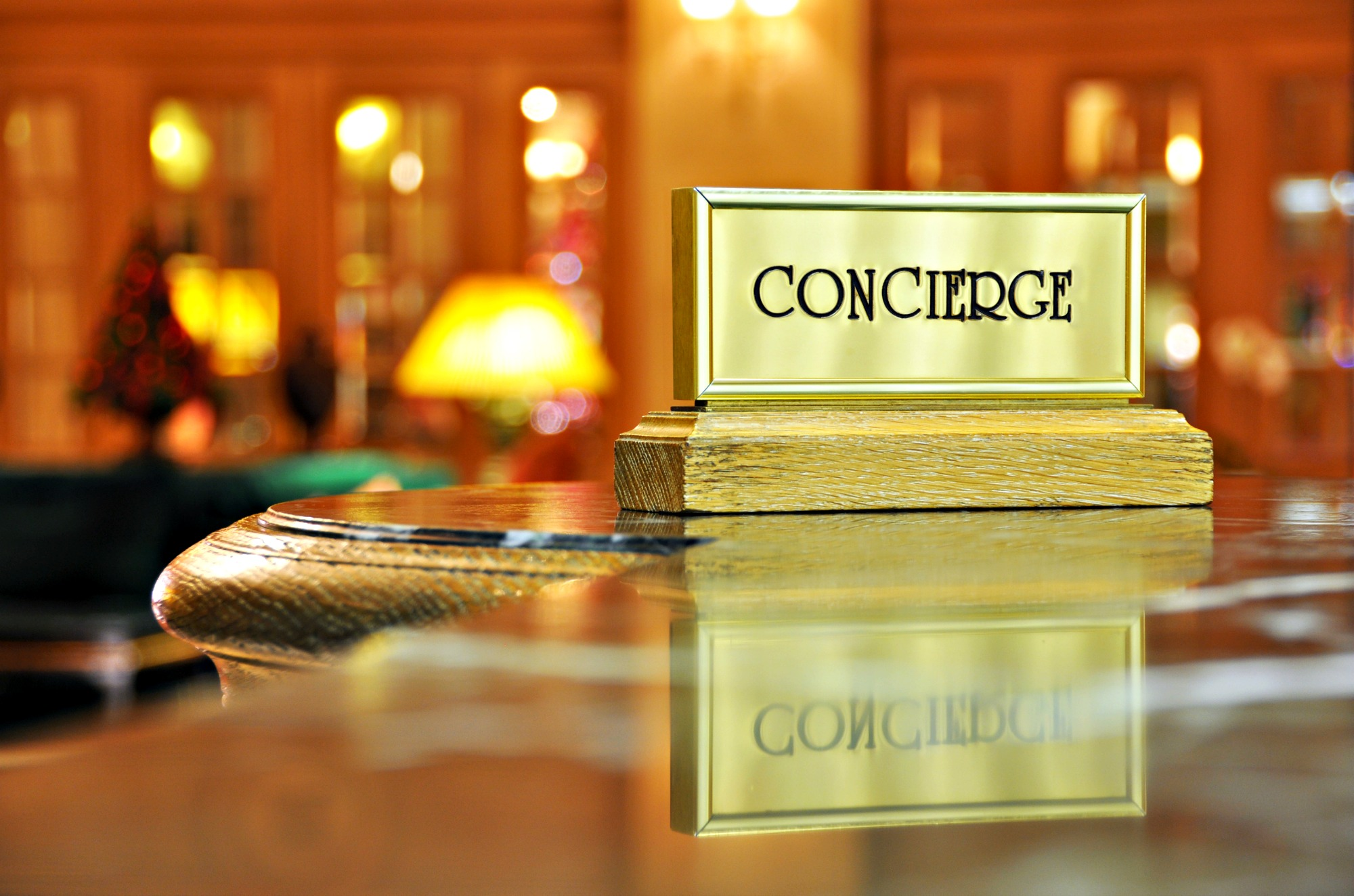 Brass concierge sign at lobby check-in desk