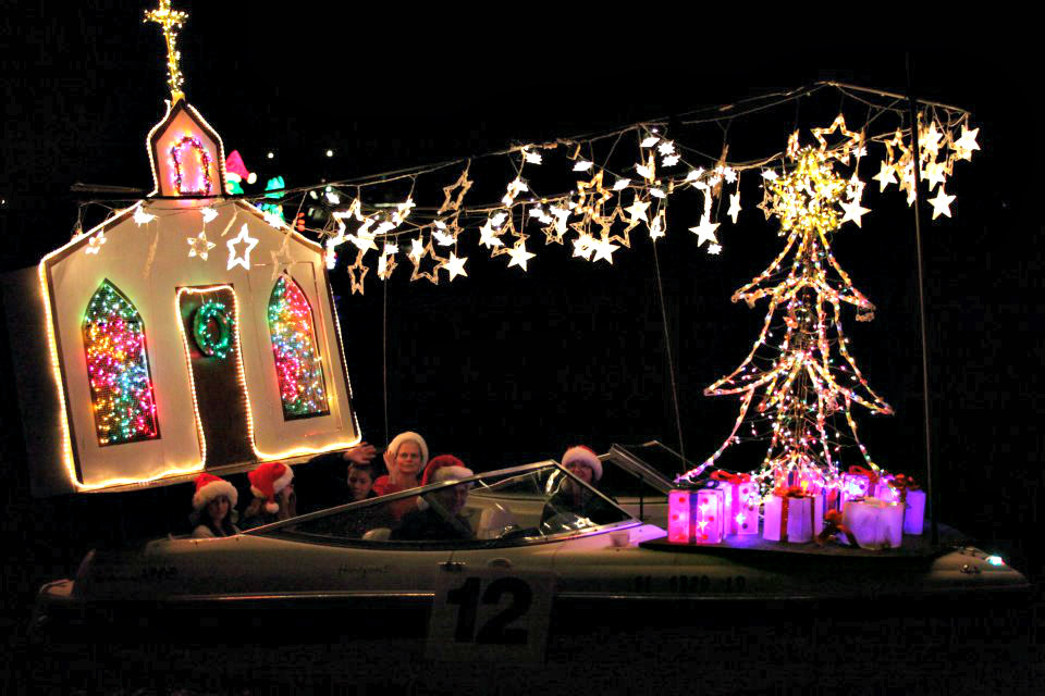 A church and Christmas tree light up this entry in the Venice, Florida, Christmas Boat Parade.