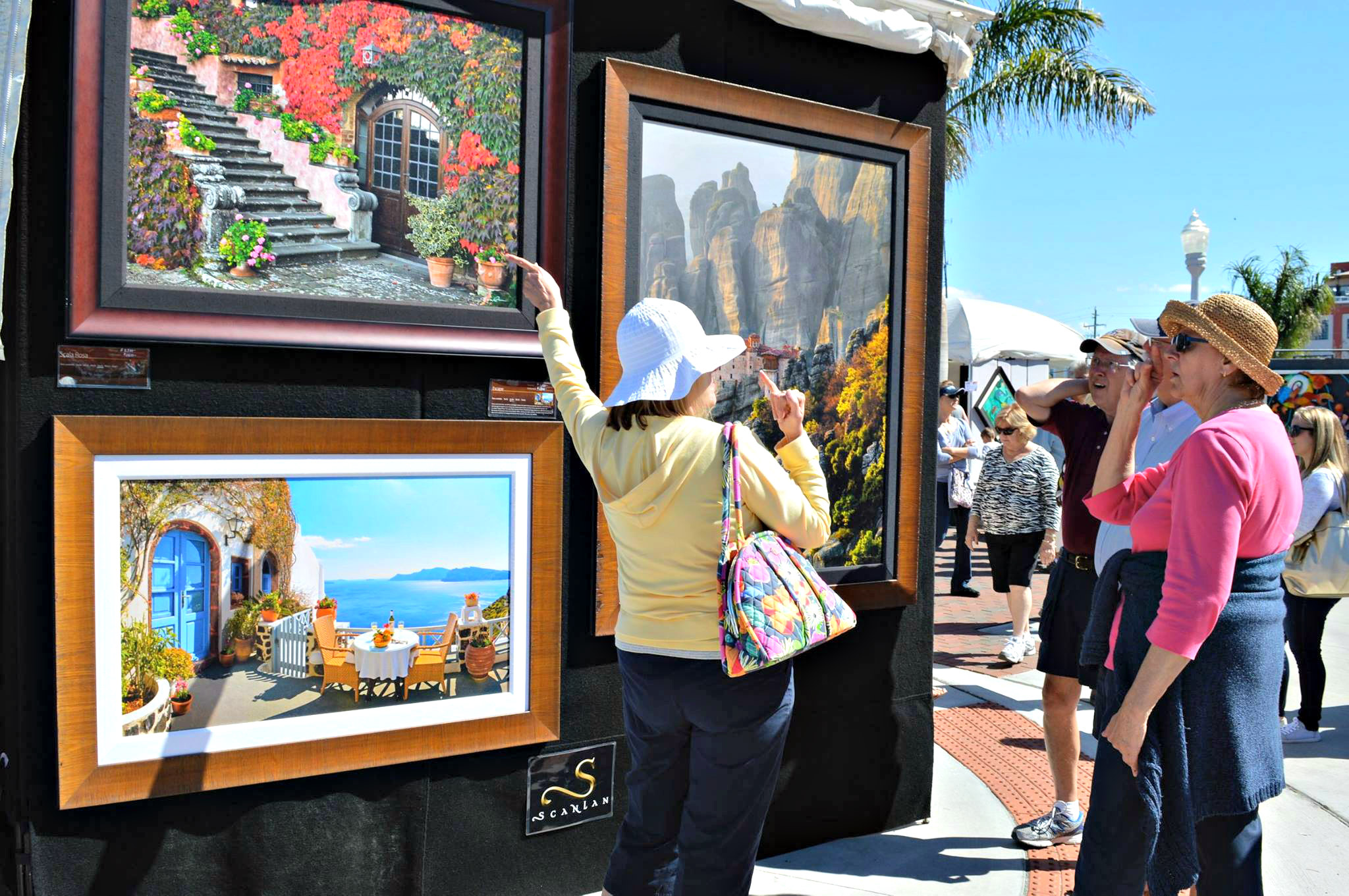 A pair of women shoppers survey an outdoor art display during ArtFest Fort Myers.