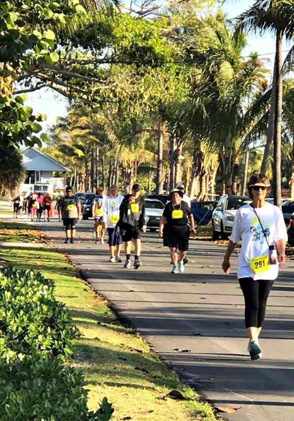 Walkers fill a tree-lined street during the Boca Grande 5K Run and Fun Walk.